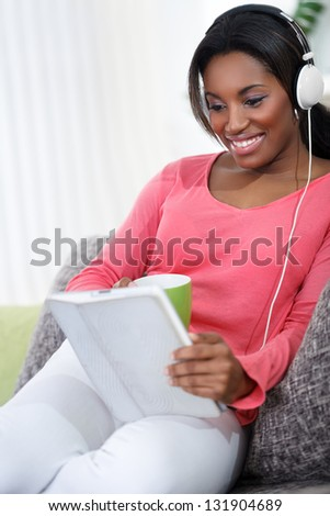 African  pretty woman sitting on sofa with tablet and listening music