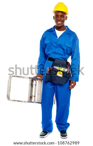African repairman holding stepladder with tool bag around his waist isolated against white background