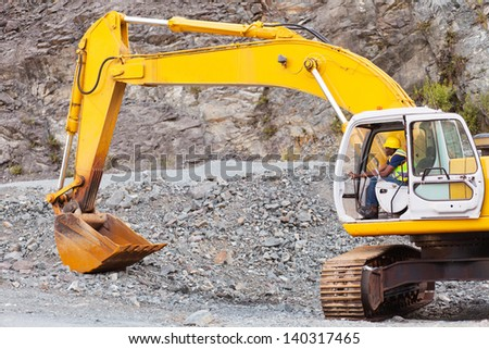 african road construction worker operating excavator on construction site - stock photo