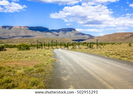 African safari in 4x4. Adventure in the African desert. Gravel mountain road in the dramatic sky, Karoo National Park in the summer, Western Cape province of South Africa.