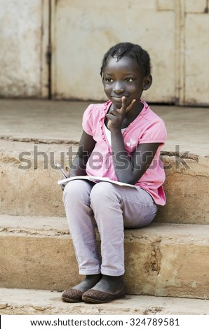 African School Girl concentrated writing notes in her exercise book, lightly smiling sitting on school stairs. Modern and proud black child, student learning her lessons outside her classroom. - stock photo