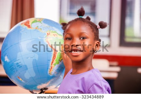 African schoolgirl learning geography with world globe. - stock photo