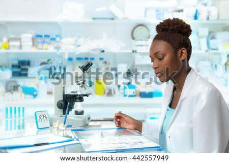 African scientist, medical worker, tech or graduate student works in modern biological laboratory - stock photo