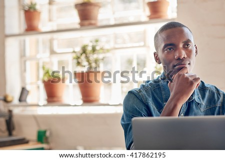 African small business owner with his laptop looking away though - stock photo