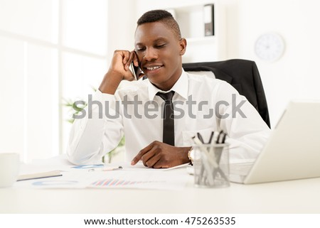 African smiling businessman sitting in the office and using smart phone.