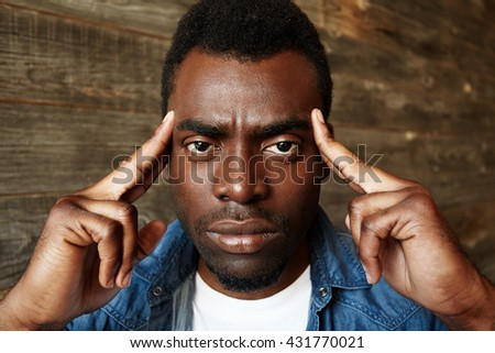 African student in denim shirt trying to remember something important while preparing for final exams at university, looking at the camera with concentrated expression, holding both hands on temples - stock photo
