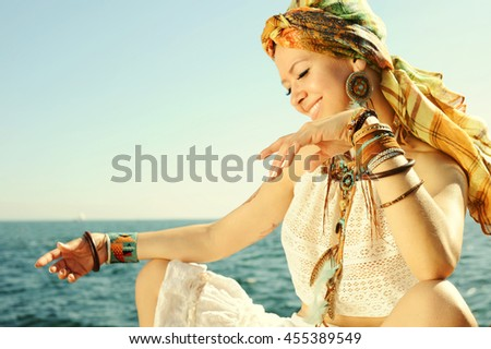African style fashion woman outdoor portrait, dressed in headband, white lace tank top, necklace and earrings, many leather wristbands, focus on a hand - stock photo