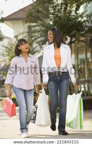 African teenaged girls carrying shopping bags - stock photo