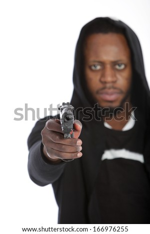 African thug aiming a gun at the camera in a threatening gesture while perpetrating a crime with focus to the gun - stock photo