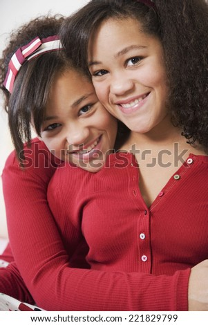 African twin sisters hugging - stock photo