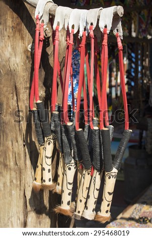 African unique traditional handmade colorful wooden rubber leather slingshots. Local craft market in South Africa. Craftsmanship. - stock photo