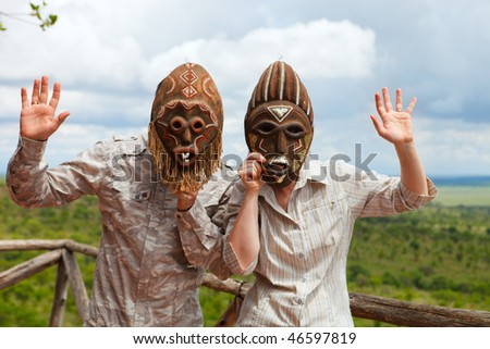 African vacation. Happy couple in african masks at balcony in safari lodge. - stock photo