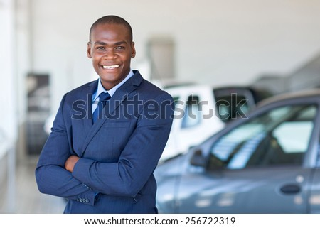 african vehicle dealership principal with arms folded in showroom - stock photo