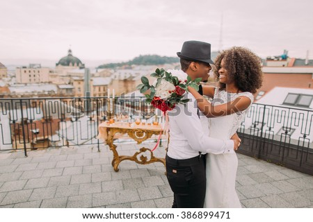 African wedding couple dances on the rooftop. Wedding day - stock photo