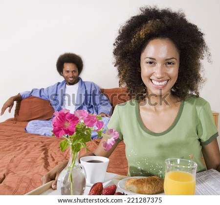African woman carrying breakfast in bed tray - stock photo