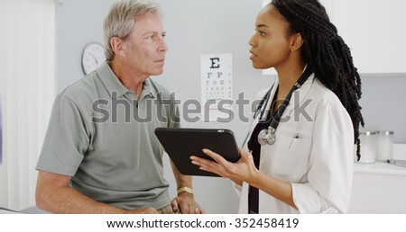 African woman doctor talking with senior patient in the office - stock photo