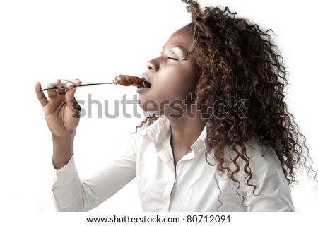 African woman eating chocolate cream - stock photo