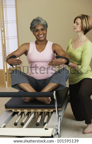 African woman exercising with personal trainer - stock photo