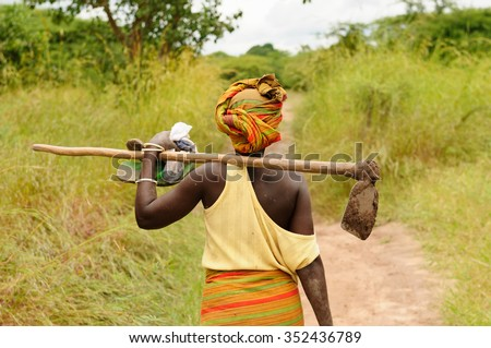 African woman going to work with the hoe in field