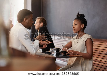 African woman having meeting with a man in busy cafe - stock photo