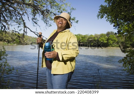 African woman hiking next to water - stock photo