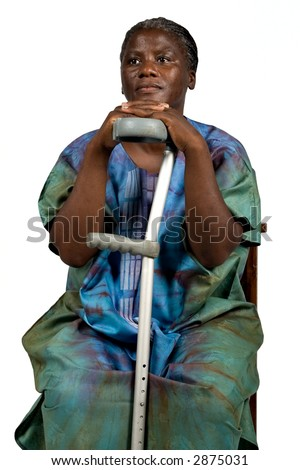 African Woman Holding a Crutch in Traditional Dress - stock photo