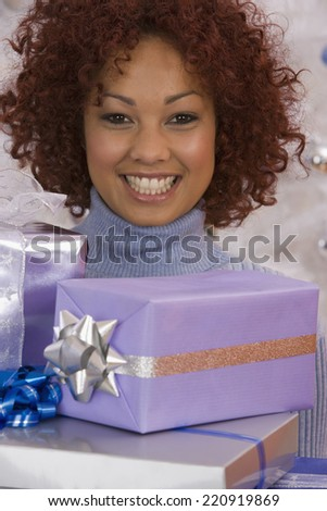African woman holding Christmas gifts - stock photo