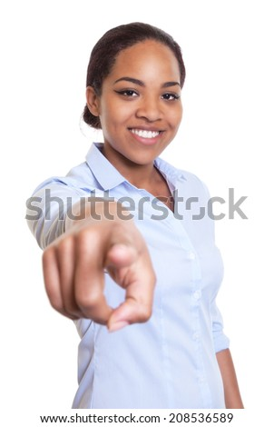 African woman in a blue shirt pointing at camera - stock photo