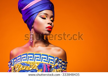 African woman in a bright dress on orange background