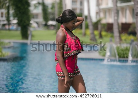 African woman in modern dress relaxing by the pool.