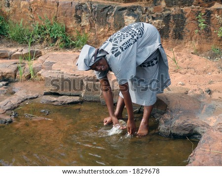 African woman in traditional printed dress washing hands. L