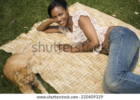 African woman laying on blanket in grass with cat - stock photo