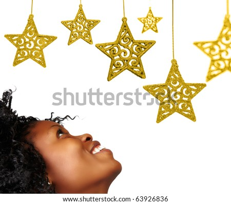 African woman looking at gold Christmas ornament stars with lace pattern isolated on white - stock photo