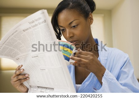 African woman reading newspaper and drinking coffee indoors - stock photo
