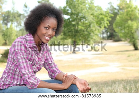 African woman relaxing in the park - stock photo
