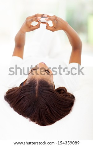 african woman sending text message while lying on bed - stock photo