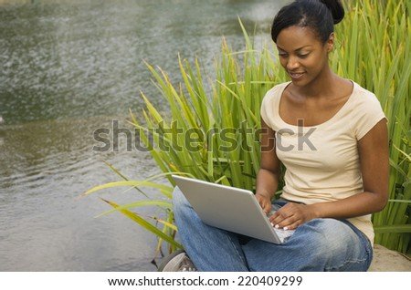 African woman sitting next to still water using laptop - stock photo