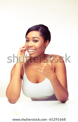 african woman speaking over the phone , looking on camera , showing thumb up - stock photo