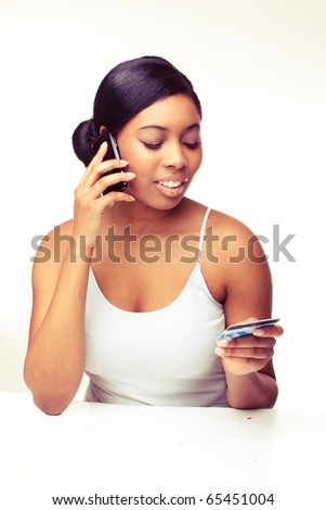 african woman speaking over the phone , paying using  credit card - stock photo