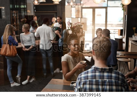 African woman talking with friend inside busy coffee shop - stock photo