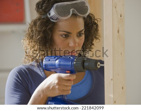 African woman using cordless drill - stock photo
