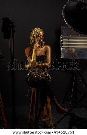 African woman wearing gold dress, headdress and evening make up with lots of shine sitting on wooden chair looking down in dark studio