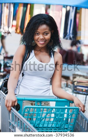 African woman with a shopping cart, smiling
