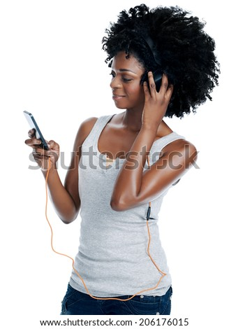 African woman with afro with headphones on listening to music from her phone isolated - stock photo