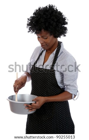African woman with curly black hair stirring a cooking mixture in a pot