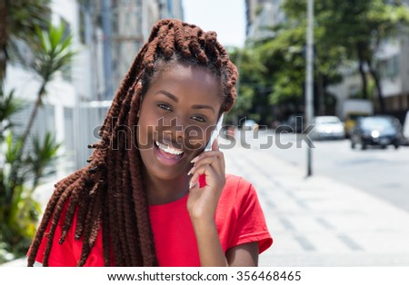 African woman with dreadlocks speaking at phone in the city - stock photo