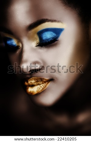 African woman with gold and blue metallic make-up and full shiny lips - stock photo