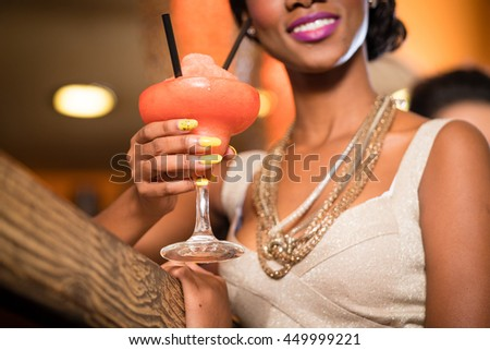 African Woman with golden necklaces in a bar drinking frozen daiquiri - stock photo