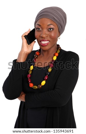 African woman with headscarf talking on her android phone. Isolated on a white background. - stock photo