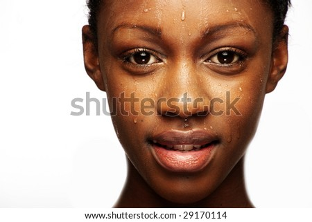African woman with natural make-up headshoot with drops on her skin - stock photo
